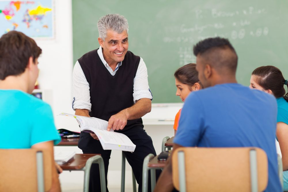 teacher teaching group of students in classroom